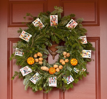 This striking variation on a colonial style outdoor wreath incorporates a variety of fresh evergreens, cloved oranges, walnuts, and playing cards.